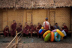An inflatable toy seller offering his wares next to a group of monks. Shwet Set Taw, Magwai<br />
