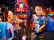 """26 FEBRUARY 2018 - BANGKOK, THAILAND: A boy backstage while adult performers put on their makeup before a Chinese Opera at the Phek Leng Shrine in the Khlong Toey section of Bangkok. The shrine traditionally hosts a Chinese Opera just after the end of Lunar New Year festivities. Thailand is home to the largest population of overseas Chinese in the world, and Chinese cultural practices, like Chinese opera, called """"ngiew"""" in Thailand, are popular. Many of the performers are ethnic Thais who don't speak Chinese. They learn their lines phonetically.     PHOTO BY JACK KURTZ"""