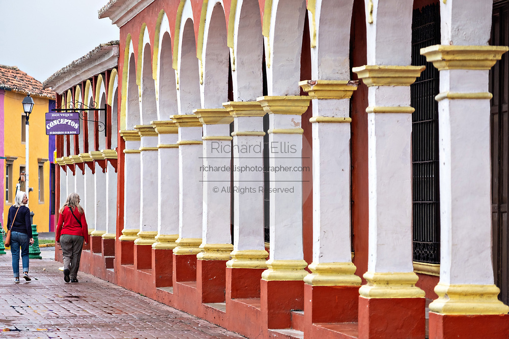 Tourists walk past the colorful colonnade style buildings in Tlacotalpan, Veracruz, Mexico. The tiny town is painted a riot of colors and features well preserved colonial Caribbean architectural style dating from the mid-16th-century.