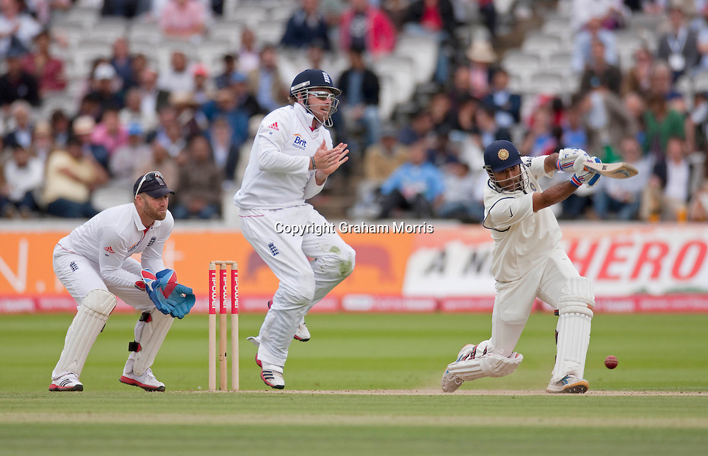 Mahendra Singh Dhoni drives past close fielder Ian Bell as wicket keeper Matt Prior watches during the first npower Test Match between England and India at Lord's Cricket Ground, London.  Photo: Graham Morris (Tel: +44(0)20 8969 4192 Email: sales@cricketpix.com) 23/07/11