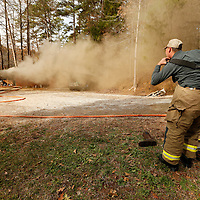 Thomas Wells | BUY at PHOTOS.DJOURNAL.COM<br /> A voluteer fireman puts on his jear to battle a house fire Friday on Lee County Road 1071 outside Guntown. There were no serious injuries but the house was heavily damaged,