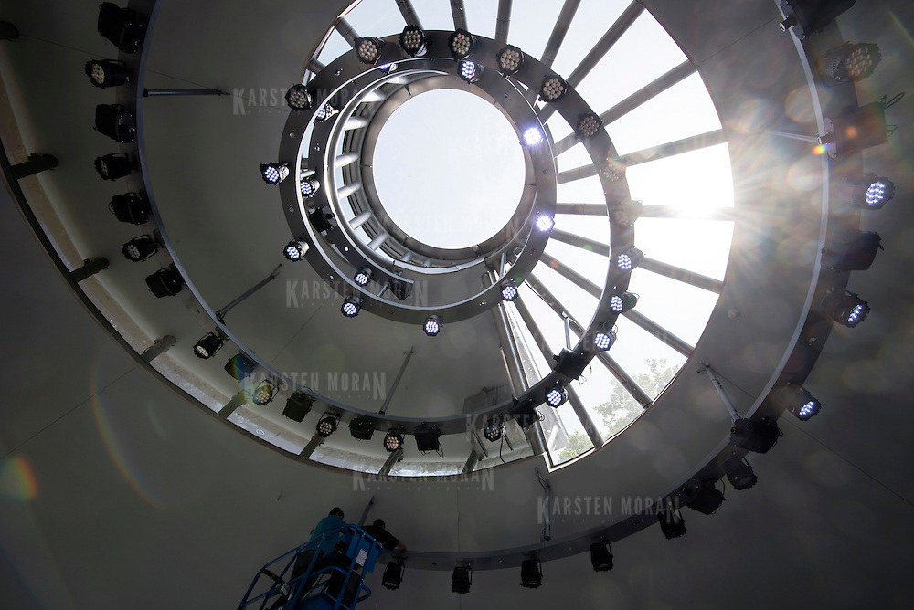 May 26, 2015 - New York, NY :  Nick Downham, left, and Eddie Muhlhausen work on the overhead lights in Seaglass Carousel on Tuesday afternoon, May 26.  A project of The Battery Conservancy, the Seaglass Carousel's structure is a spiraling pavilion of glass and steel, designed by WXY Architecture to resemble a chambered nautilus. CREDIT: Karsten Moran for The New York Times