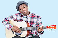 Portrait of a young man playing guitar over light blue background