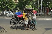 Men unloading a farmers produce from the ricksha