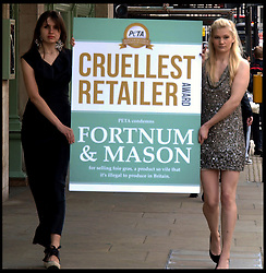 Two PETA activists walk past the Fortman & Mason department store in London, after it received the animal welfare group's 'Cruellest Retailer Award' for still selling 'foie gras'  (Goose Liver) , although its manufacture in Britain is outlawed, London, UK, Monday May 13, 2013. Photo by: Max Nash / i-Images