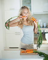 Woman eating carrot at kitchen counter