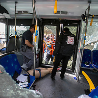 An Israeli forensic police officer inspects the body of Palestinian terrorist at the scene of a shooting attack in Jerusalem, Tuesday, Oct. 13, 2015. A pair of Palestinian men boarded a bus in Jerusalem and began shooting and stabbing passengers, while another terrorist rammed a car into a bus station before stabbing bystanders, in near-simultaneous attacks. <br />