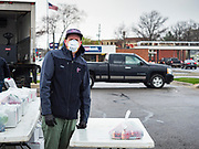 """11 APRIL 2020 - DES MOINES, IOWA: JORDON ELWELL, owner and CEO of Midwest Foods, waits for a motorist to pick up a ready to cook pasta meal during a food distribution in Des Moines. Most non-essential businesses in Iowa are closed until 30 April. Because of business closings causes by the Novel Coronavirus (SARS-CoV-2) pandemic, well over 100,000 Iowans filed first time claims for unemployment in the last three weeks, more than applied during the peak of the Great Recession of 2008. Local food banks have seen an unprecedented spike in people seeking nutritional assistance. Midwest Foods, a Des Moines based company and owner of Ginos Fine Italian Foods, gave away 1,000 complete dinners with sauce, noodles, salad, and dressing Saturday morning. People started lining up 3 hours before the food distribution began. The food distribution was done following """"social distancing"""" guidelines and all of the workers wore masks and gloves.       PHOTO BY JACK KURTZ"""