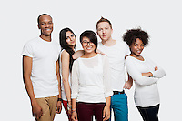 Portrait of multi-ethnic friends in casuals smiling together over white background