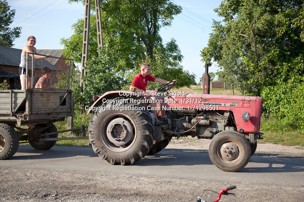 Polish man driving tractor and cart carrying two women along village lane. Mala Wola Central Poland