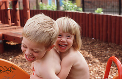 Brother and sister sitting on trike in children's playground hugging each other,