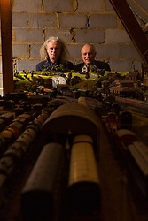 Brothers Simon, 53 and Paul Hurst, 58 have some of their late father's ashes carried around his extensive model railway in the loft of his home. PICTURED: Simon, left, and Paul admire their late father Peter's model railway, built into the loft above his home. Leeds, Kent, March 15 2018.