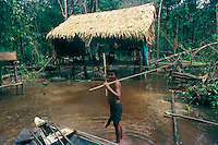 ca. 1986, Near Manaus, Brazil --- mestizo boy with fishing spears near his family's thatched hom en the Brazilan Amazon --- Image by © Owen Franken