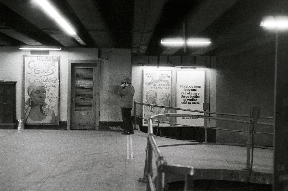Man making a private or secret telephone call. Grand Central Terminal. Unpopulated area. Posters of two Broadway plays and Playboy magazine. Isolated and hidden. Financial crisis in New York City. 1975.