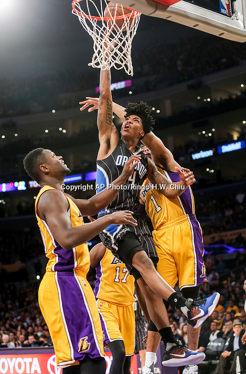 Orlando Magic guard Elfrid Payton, center, goes up for a lay up against Los Angeles Lakers forward Julius Randle, left, and guard D'Angelo Russell during the first half of an NBA basketball game Tuesday, March 8, 2016, in Los Angeles.  (AP Photo/Ringo H.W. Chiu)