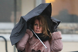 © Licensed to London News Pictures. 19/02/2015. Brighton, UK. A woman battles to keep her umbrella to shelter from the rain in Brighton. High winds and waves are battering the South Coast Photo credit : Hugo Michiels/LNP
