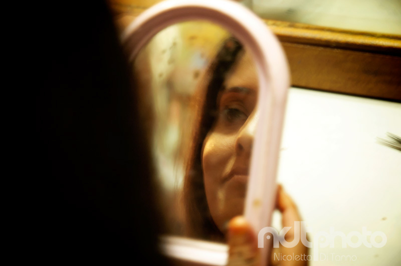 A woman looks at herself in the mirror after hairdressing. Rajasthan, India