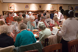 Elderly people eating meals in function room,