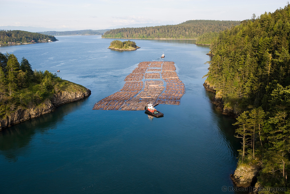 Two tugboats navigating a log raft through a narrow passage in the Pacific Northwest.