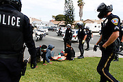 Police circle and tell four Anti-Trump protestors to take off mask and to lay down May 25, 2016 in Anaheim, California.