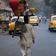 A man carries a tray of gol gappa on his head and a chair on his arm on way to the location where he will put up his stand for the evening, Kolkata, January 2007