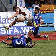 A New South Wales CRL player shows his athleticism and sportsmanship while avoiding a Toa Samoa Resident Team player who scored a try during their rugby league game at Apia Park, Apia, Samoa.  Photo by Barry Markowitz, 10/8/16