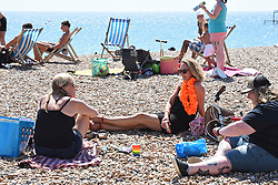 © Licensed to London News Pictures. 30/05/2020. Brighton, UK. Members of the public relax in the hot weather on a busy Brighton seafront in East Sussex, during lockdown to prevent to spread of COVID-19.  Photo credit: Liz Pearce/LNP
