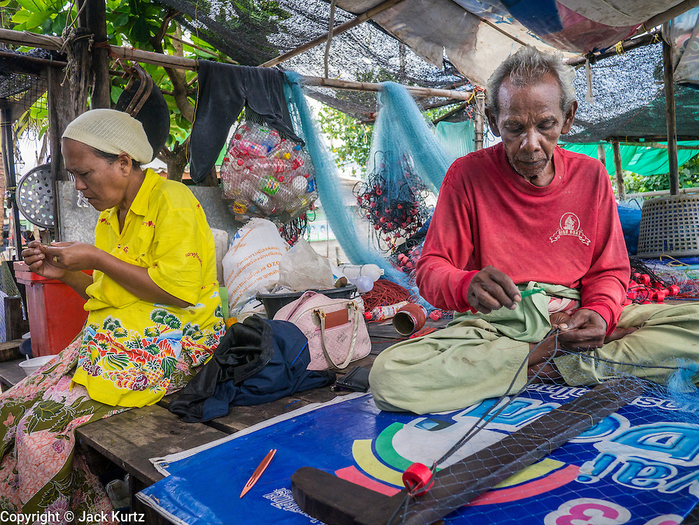 04 NOVEMBER 2012 - KAO SENG, SONGKHLA, THAILAND:  A fisherman repairs his nets in Kao Seng. Kao Seng is a traditional Muslim fishing village on the Gulf of Siam near the town of Songkhla, in the province of Songkhla. In general, their boats go about 4AM and come back in about 9AM. Sometimes the small boats are kept in port because of heavy seas or bad storms.    PHOTO BY JACK KURTZ