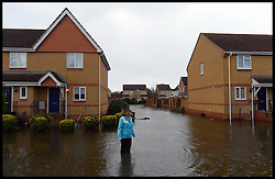 A resident of Egham wades through flood water in an housing estate in flood hit  Egham, Surrey, United Kingdom, as floods hit Britain. Thursday, 13th February 2014. Picture by Andrew Parsons / i-Images