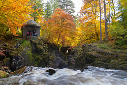 Dunkeld, Perthshire, Scotland, United Kingdom, 10th October 2018.  Spectacular autumn colours in the trees at The Hermitage a famous beauty spot near Dunkeld in Perthshire. Pictured is Ossian's Hall overlooking the River Braan.