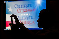 A new U.S. citizen takes a photograph using an smartphone during a naturalization ceremony at the Evo A. DeConcini U.S. Courthouse in Tucson, Arizona, U.S., on Friday, Sept. 16, 2016. Photographer: David Paul Morris/Bloomberg