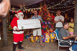 Dan Whalen, center, donates to the Humane Society on behalf of his organization Boatacon.  Christmas Tree Lighting and Seasonal Fundraiser for the Humane Society of St. Thomas.  St. Thomas, USVI.  11 De© Aisha-Zakiya Boyd