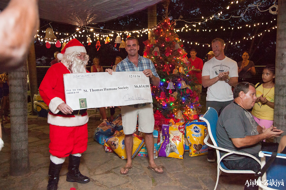 Dan Whalen, center, donates to the Humane Society on behalf of his organization Boatacon.  Christmas Tree Lighting and Seasonal Fundraiser for the Humane Society of St. Thomas.  St. Thomas, USVI.  11 De© Aisha-Zakiya Boyd