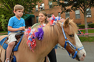 Garden City, New York, U.S. - June 6, 2014 -  A young boy rides a pony at the Garden City Belmont Stakes Festival, celebrating the 146th running of Belmont Stakes at nearby Elmont the next day. There was street festival family fun with live bands, food, and more, and a main sponsor of this Long Island night event was The New York Racing Association Inc.