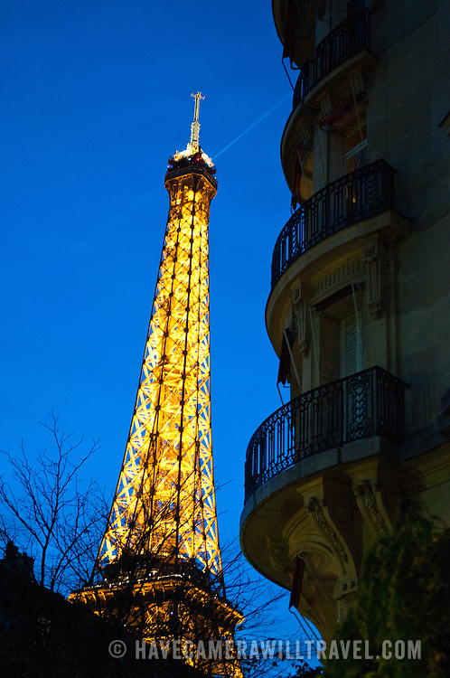 The Eiffel Tower illuminated at night against a deep blue sky of dusk. At right is the silhouette of a nearby apartment building.