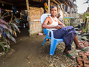 11 NOVEMBER 2014 - SITTWE, MYANMAR:  A Rakhine Buddhist relaxes in front of his thatched home in a Rakhine IDP camp near Sittwe. About 700 Rakhine Buddhist families live in an Internal Displaced Persons (IDP) camp on the edge of Sittwe. The people in the camp lost their homes in Sittwe in 2012 when Buddhist mobs rioted and burnt down Rohingya Muslim homes and businesses. The Buddhists' homes were mistakenly destroyed by other Buddhists or intentionally destroyed by retaliating Muslims during the 2012 violence. Unlike the Muslims, who live in much larger camps further from Sittwe, the Buddhists are allowed to come and go into downtown Sittwe and their homes are built in the traditional style, on stilts with large windows, and so are much more comfortable.  PHOTO BY JACK KURTZ