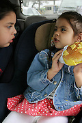 (MODEL RELEASED IMAGE). After going grocery shopping, Brian and Brianna Fernandez devour Texas-size pan dulces from their local San Antonio, Texas supermarket in the back of the family minivan. (Supporting image from the project Hungry Planet: What the World Eats.)