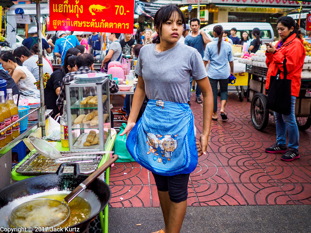 "18 MAY 2017 - BANGKOK, THAILAND: A woman gets ready to make deep fried appetizers at a street food stall in Bangkok's Chinatown. City officials in Bangkok have taken steps to rein in street food vendors. The steps were originally reported as a ""ban"" on street food, but after an uproar in local and international news outlets, city officials said street food vendors wouldn't be banned but would be regulated, undergo health inspections and be restricted to certain hours on major streets. On Yaowarat Road, in the heart of Bangkok's touristy Chinatown, the city has closed some traffic lanes to facilitate the vendors. But in other parts of the city, the vendors have been moved off of major streets and sidewalks.      PHOTO BY JACK KURTZ"