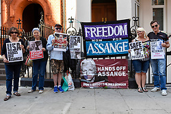 © Licensed to London News Pictures. 01/08/2018. LONDON, UK. Julian Assange supporters pose with their signs outside the Ecuadorean Embassy in Knightsbridge. The UK and Ecuador are holding ongoing talks over the fate of Wikileaks founder Julian, who has been in exile in the Ecuadorean Embassy since 2012.  He faces being arrested by UK police if he leaves the embassy for breaching bail conditions.  Photo credit: Stephen Chung/LNP