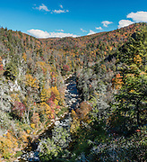 From Chimney View Overlook in Linville Gorge Wilderness Area, see vivid fall foliage colors in mid October. Walk to see impressive Linville Falls, in Burke County, Pisgah National Forest, North Carolina, USA. Linville Falls drop 90 feet in a multi-level cascade, viewable from several overlooks along two trails starting from Linville Falls Visitors Center, run by the National Park Service. Directions: Turn eastwards at Mile Post 316.3 of the Blue Ridge Parkway (north of where US 221 crosses the Parkway and south of where NC 181 crosses). Linville River begins at Grandfather Mountain and enters the 12-mile Linville Gorge at Linville Falls. Linville Gorge, near the town of Linville Falls (66 miles north of Asheville), is the deepest and one of the most rugged and scenic gorges in the Eastern USA (qualifying for the nickname Grand Canyon of the East, along with more than a dozen chasms likewise tagged in other Eastern states). It is protected by Linville Gorge Wilderness Area, within Pisgah National Forest. Spared by its rugged terrain from clear-cutting in the early 1900s, Linville Gorge has some of the best remnant stands of uncut, old-growth forest in the southern Appalachians. This is one of the few places where the Rosebay, Catawba, and Carolina rhododendron grow side by side. This panorama was stitched from 3 overlapping photos.