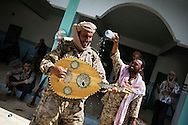 LIBYAN ARAB JAMAHIRIYA, GAZAIA : A Libyan rebel fighter plays a traditional oud instrument after rebels took control of the southwest village of Gazaia, on July 28, 2011, in Gazaia. ALESSIO ROMENZI