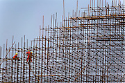 Workers assemble scaffolding on the construction site of a new 50,000-seat sports stadium in Conakry, Guinea on Friday March 6, 2009.  The project, an investment of about USD 50 million, is a gift to Guinea from the Chinese government.(Olivier Asselin for the New York Times).