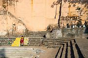 Woman with washing on the steps of Banganga Tank, Mumbai.
