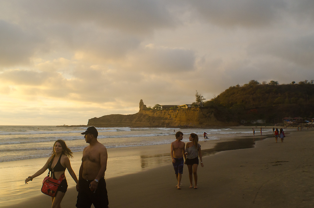 Couples walking at dusk in the surf in the beach town of Montañita, Ecuador.