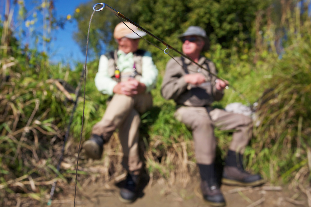 Stuart Crooks (left) and Lawrence Greasley, flyfishermen from the UK, taking a rest at the banks of the San River. Myczkowce, Poland.