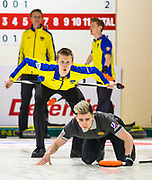 Axel Sjoeberg of Sweden watches over Daniil Goryachev of Russia's shoulder as Goryachev's shot makes its way down the sheet during round-robin action at the 2016  VoIP Defender World Junior Curling Championships. The Russian men's team was relegated to the junior-b world championships in 2017.