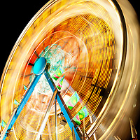 Picture of Carnival Ferris Wheel at night spinning motion blurred. Photo is high resolution.