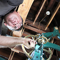 Richard Hogan of the Monroe County Building and Grounds Department adjusts the time on the county courthouse's clock from its bell tower. The clock hadn't rung in three years before the recent work.