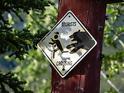 """Tourists Crossing"" sign shows a bear delightfully chasing a person with camera. Cottonwood RV Park, Kluane Lake, Yukon, Canada."