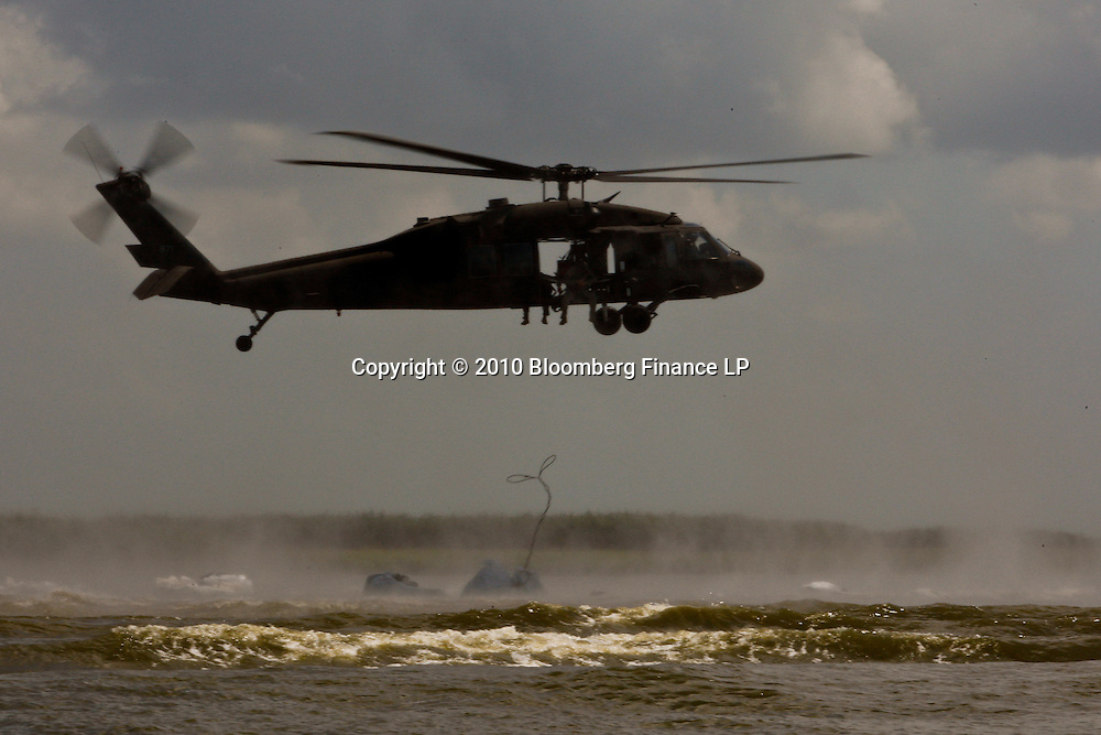A National Guard, Blackhawk Helicopter drops sand bags off the coast near Venice, Louisiana, U.S., on Sunday, June 27, 2010. The BP Plc oil spill, which began when the leased Transocean Deepwater Horizon oil rig exploded on April 20, is gushing as much as 60,000 barrels of oil a day into the Gulf of Mexico, the government said. Photographer: Derick E. Hingle/Bloomberg..